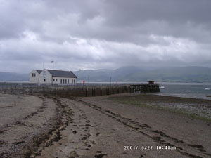 Low water at Beaumaris on a dull and windy day. View at 0941 GMT on 29 June across the Menai Strait shows the 'Blue Peter' Lifeboat Station and the cloud covered Snowdonia Mountains. Photo: © D.Perkins 2000.