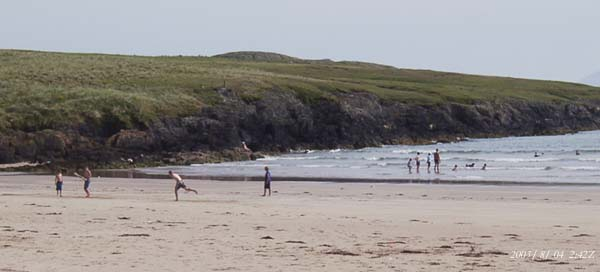 The sky lost much of its blue colour as a dust plume arrived from north Africa. Locals and holidaymakers enjoying the sea and sand at Traeth Aberffraw, including traditional cricket, on 4 August 2003