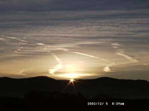 The moment of sunrise over the Carneddau Mountains photographed from Llansadwrn Weather Station on 5 December 2003. Click to see larger image.
