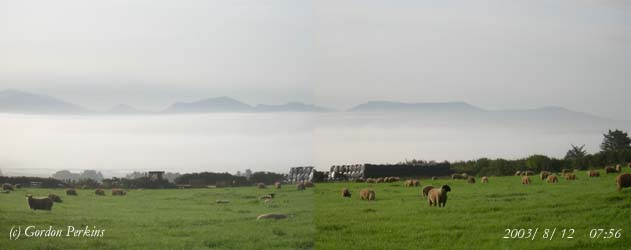 Inversion fog in the Cefni Estuary on the morning of the 12 August 2003. Mountains on the Lleyn Peninsular clear in the background. Photo: © Gordon Perkins.