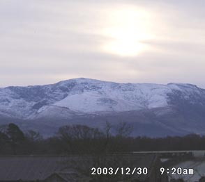 Sun obscured by thin cloud above snow on the Carneddau Mountains on 30 December 2003. Click to see larger image.