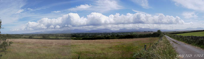 Linear cumulus cloud formation over Snowdonia. Centre view is looking S from Llangeinwen (SW Anglesey) over the village of Dwyran towards Caernarfon and Yr Wyddfa (Snowdon) above. On the left are the Carneddau and on the right the water in Caernarfon Bay and mountains of the Lleyn Peninsula.