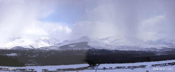 Snow showers driven by a strong NE'ly wind (left to right) move across the Snowdonia Mountains on the afternoon of 27 February 2004. From the left Carneddau, Nant Ffrancon Pass with the summit of Tryfan, Mynedd Perfedd and Elidir Fach with Glyders behind, Llanberis Pass and Snowdon on the right.