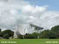 Cumulus clouds form backcloth for Jodrell Bank radio telescopes.