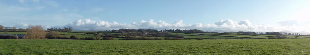 Llansadwrn view towards Gadlys and the mountains on a sunny afternoon.